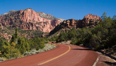 Red road leading to large monoliths formed by water erosion formed by the Virgin River n Zion National Park Utah Imagens