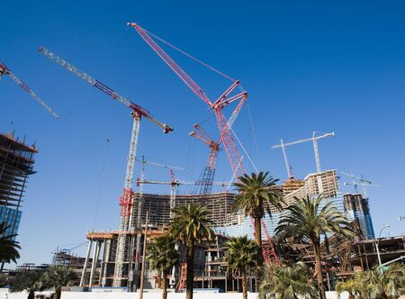 erecting: Building under construction with large cranes aid palm trees in the foreground