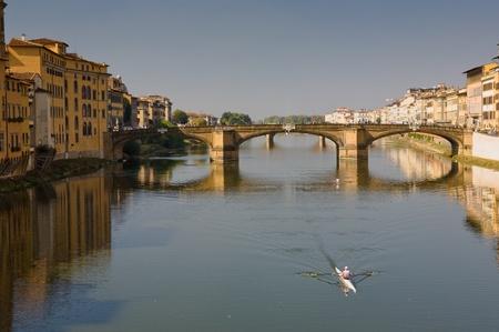 イタリア、フィレンツェ、アルノ川沿い川沿いの建物とボート 写真素材