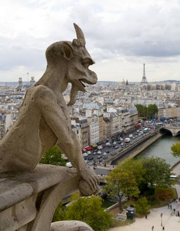 Gargoyle on Notre Dame Cathedral overlooking the city of Paris France