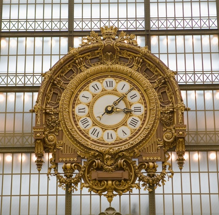 clock: Extremely large, golden colored clock inside Musee dOrsay Museum in Paris, France, which contains contemporary artwork