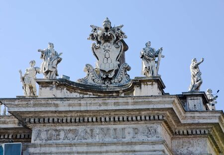 Statues along the rood line of a building in St. Peter�s Square, Vatican City on a sunny day photo