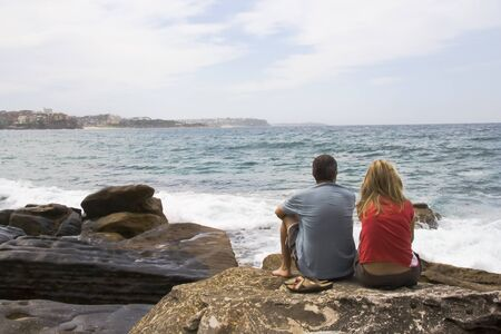 Couple sitting on the rocks at Maly beach, New South Wales, Sydney, Australia