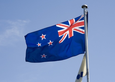 New Zealand flag blowing in the breeze against a blue sky.