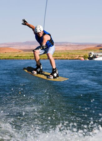 Wakeboarder boarding behind a boat with beautiful Lake Powell in the background at Glen Canyon National Recreation Area, Utah, USA Stock Photo - 9504407