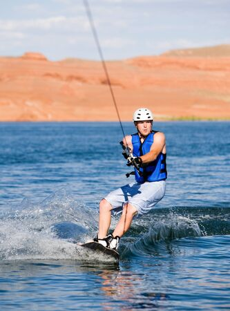 Wakeboarder boarding behind a boat with beautiful Lake Powell in the background at Glen Canyon National Recreation Area, Utah, USA Stock Photo - 9504443