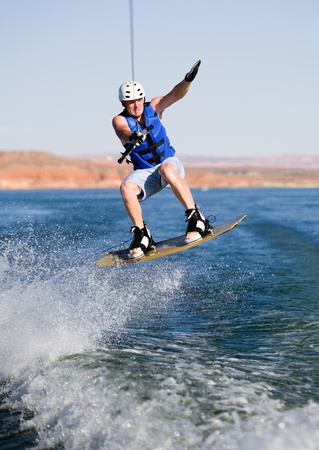 Wakeboarder boarding behind a boat with beautiful Lake Powell in the background at Glen Canyon National Recreation Area, Utah, USA Stock fotó
