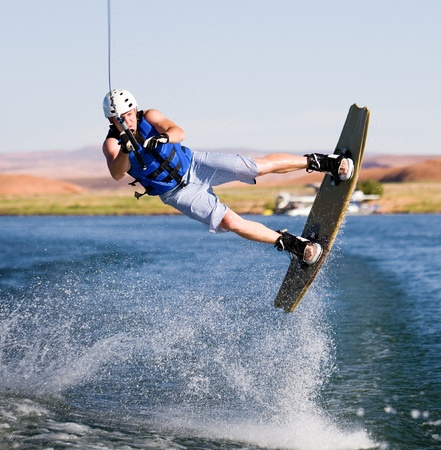 lake powell: Wakeboarder boarding behind a boat with beautiful Lake Powell in the background at Glen Canyon National Recreation Area, Utah, USA Stock Photo