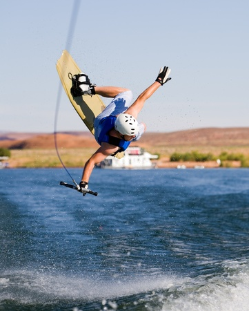 water skiing: Wakeboarder boarding behind a boat with beautiful Lake Powell in the background at Glen Canyon National Recreation Area, Utah, USA Stock Photo