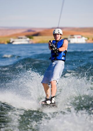 Wakeboarder boarding behind a boat with beautiful Lake Powell in the background at Glen Canyon National Recreation Area, Utah, USA photo