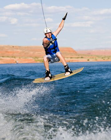 Wakeboarder boarding behind a boat with beautiful Lake Powell in the background at Glen Canyon National Recreation Area, Utah, USA Stock Photo