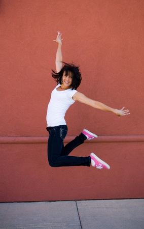 Young attractive girl jumping for joy on a sidewalk with a red wall background photo