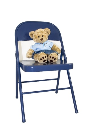 A cute brown bear wearing a blue out fit and sitting on a chair
