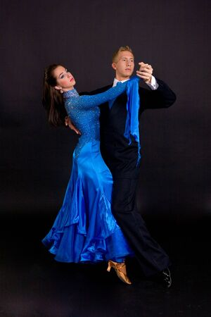 Young ballroom dancers in formal costumes posing against a solid background in a studio