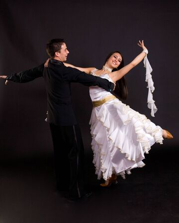 Young ballroom dancers in formal costumes posing against a solid background in a studio photo