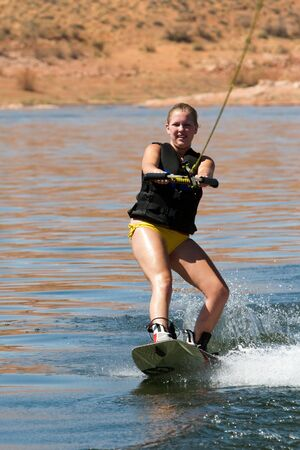 Girl wakeboarder enjoying water sports boarding   behind a boat with beautiful Lake Powell in   the background at Glen Canyon National   Recreation Area, Utah, USA photo
