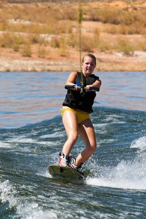Girl wakeboarder enjoying water sports boarding   behind a boat with beautiful Lake Powell in   the background at Glen Canyon National   Recreation Area, Utah, USA Stock Photo - 11819914