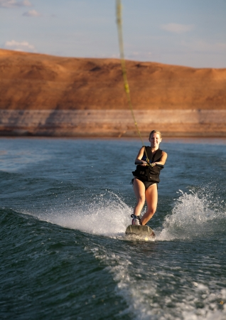 lake powell: Young woman wakeboarding at Lake Powell in the southwestern US desert  Stock Photo