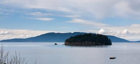 puget sound: Piccola isola coperta di alberi in Puget Sound, Washington, con le montagne sullo sfondo