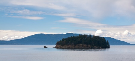 puget: Tiny Island covered with trees in Puget Sound, Washington with mountains in the background