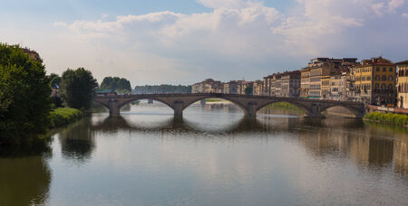 Bridge in Florence, Italy with colorful buildings on a sunny day.