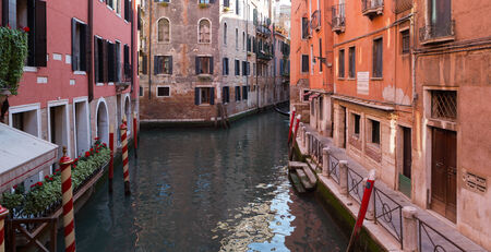 Quiet Venice, Italy canal lined with colorful buildings in summer