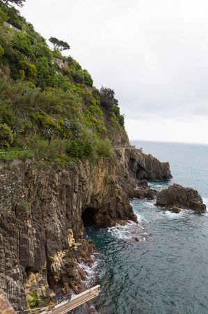 Green cliffs along the Mediterranean ocean in Cinque Terre, Italy.