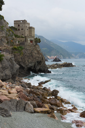 Beach and tower along the Mediterranean ocean in Monterosso in Cinque Terre, Italy.