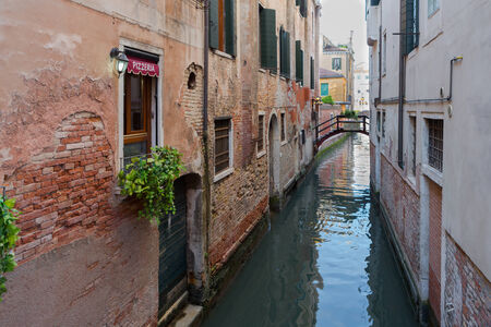 Quiet canal in daylight with small bridge in Venice, Italy Editorial