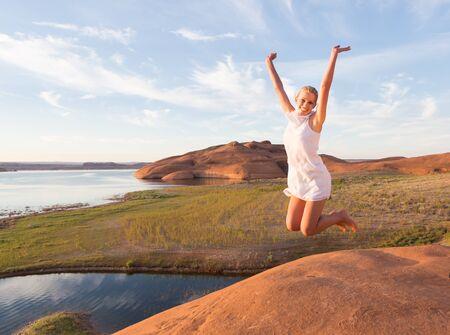 exuberance: Girl raising her arms in success beside a desert lake at sunrise.