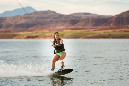wakeboarding: Girl wake boarding at Lake Powell, Utah in the summer sunshine.