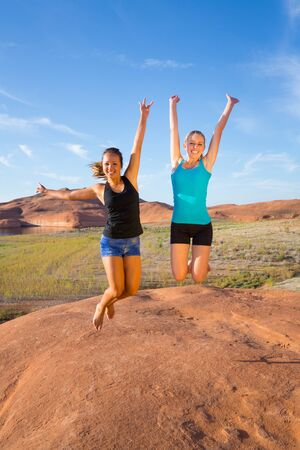 exuberance: Two girls jumping for joy and happiness in the desert sunshine at sunrise. Stock Photo
