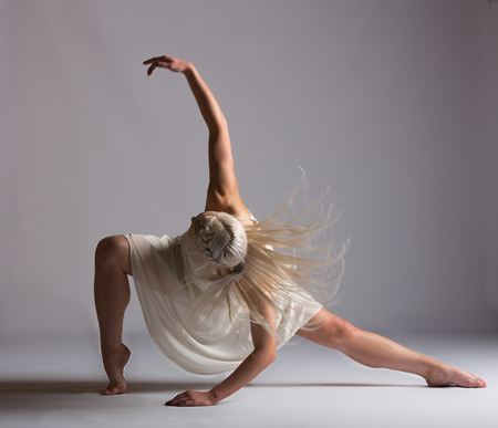 Girl contemporary dancer in studio against a white background in cr�me colored dress