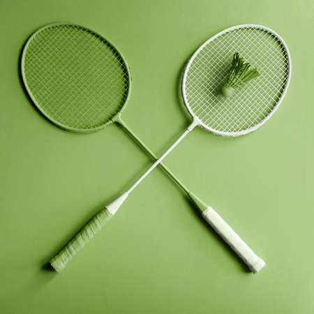 Green badminton racket on green background. Creative fashion sports series. Greenery