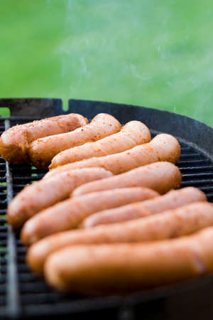 grill tongs sausage: A lot of sausages on a grill