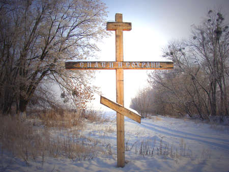 Winter Landscape with a wooden cross in the foreground photo