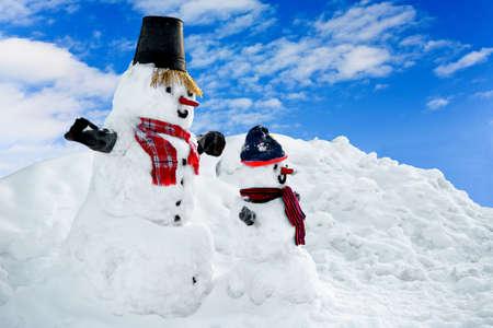 大人の雪だるまと背景の空に雪だるま子