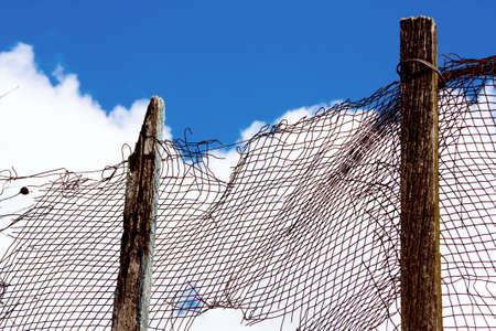 netlike: Old netlike fence on a sky background