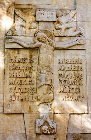 Crucifix on the wall of ancient temple. The text on a bas-relief means:But he was wounded for our transgressions, he was bruised for our iniquities, the chastisement of our peace was upon him, and with his stripes we are healed.(53:5 The Book of the Pro photo