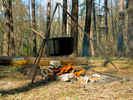 Cooking outdoors in cast-iron cauldron photo