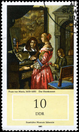 GDR - CIRCA 1982: A Stamp printed in GDR shows the painting Music Making at Home, of the artist Frans van Mieris (1635-1681), from the series 17th Cent. Paintings in Natl. Museum, Schwerin, circa 1982 Stock Photo
