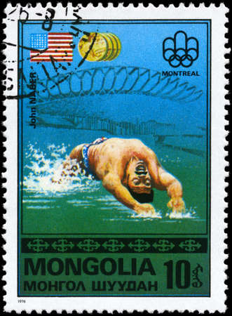 MONGOLIA - CIRCA 1976: A Stamp printed in MONGOLIA shows the John Naber, Montreal Games� Emblem, US Flag, Gold Medals from the series Gold medal winners, 21st Olympic Games, Montreal, Canada, circa 1976