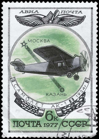 perforated stamp: USSR - CIRCA 1977: A Stamp printed in USSR shows the Aviation Emblem and AK-1 monoplane (1924), from the series Aviation 1917-1930, circa 1977