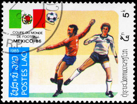 LAOS - CIRCA 1985: A Stamp printed in LAOS shows the Soccer Players, Football Field and flag of Mexico, series, circa 1985 photo