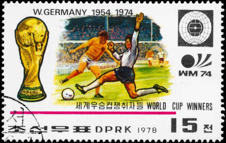 NORTH KOREA - CIRCA 1978: A Stamp printed in NORTH KOREA shows the Soccer players, Cup, Emblem and Globe, Germany (1954, 1974), World Cup Winners, circa 1978