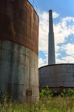 Landscape of the old sugar refinery with tanks and smoke stack