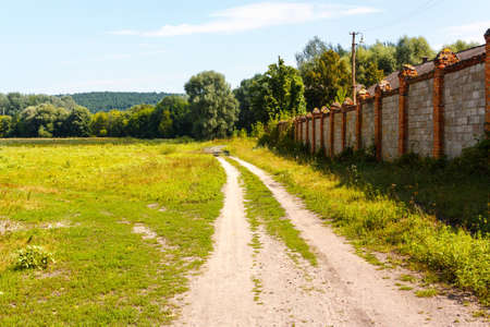 Landscape with dirt road and brick fence