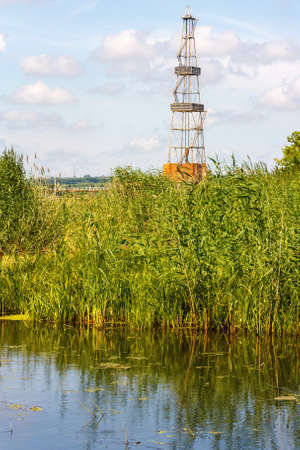 Landscape with the oil derrick and river