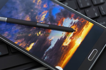 stylus pen: Modern phablet with a stylus pen and with sunset picture on the screen