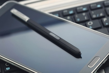 stylus pen: Phablet with stylus pen on laptop keyboard